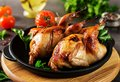 Baked quails in pan on a dark background Royalty Free Stock Photo