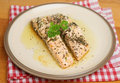 Baked salmon fillets in olive oil lemon juice and herbs Stock Image
