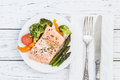 Baked salmon with vegetables on plate. White wooden table Royalty Free Stock Photo