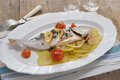 Baked sea bream with vegetables on an oval dish Stock Photo