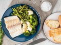 Baked sea fish cod fillet with vegetables on blue plate, bread,