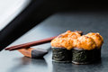 Baked sushi roll on dark background with chopstick Stock Photo
