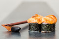 Baked sushi roll on grey background with chopstick Stock Images