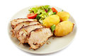 Baked tenderloin garnished with potatoes lettuce and tomatoes o closeup of a on a plate Stock Photography