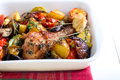 Baked vegetables and chicken drumstick in baking tin Stock Photos