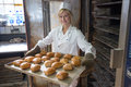 Baker in bakehouse or bakery putting bread in the oven a tablet of buns into an Royalty Free Stock Photo