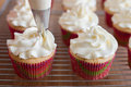 Baker decorates muffins with cream and confectionery nozzles Royalty Free Stock Photo