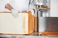 Baker holding big bread loaf at cutting machine in bakery midsection of male Stock Photography
