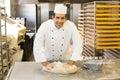Baker kneading dough in bakery Royalty Free Stock Photo