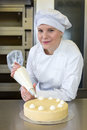 Baker prepares cake in bakehouse with whipped cream