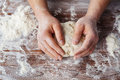 Baker prepares the dough on a wooden table, male hands knead the dough with flour Royalty Free Stock Photo