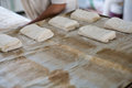 Baker prepping ciabatta bread buns a bakery placing freshly prepped raw roll on a tray Stock Image
