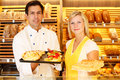 Baker and shopkeeper present pastry bakery different types of in shop Royalty Free Stock Photo