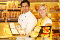 Baker and shopkeeper present pastry bakery different types of in shop Royalty Free Stock Images