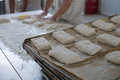 Baker and tray of fresh ciabatta bread buns a with hands in flour prepping rolls that show in the forground Royalty Free Stock Images