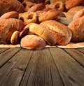 Bakery bread food concept on an old fashioned wood table background with a group of baked goods made from whole wheat and natural Stock Images