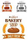 Bakery shop logo with fresh bread emblem or depicting hot loaf of rye bordered golden wheat ears and ribbon banner text daily Royalty Free Stock Photos
