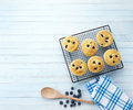 Baking background blueberry muffins on a cooling rack with wooden spoon towel and blueberries on a light blue Stock Image