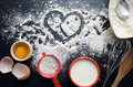 Baking ingredients on a dark, stone table: eggs, flour and milk Royalty Free Stock Photo