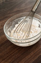 Baking and mixing flour butter milk egg ingredients in a glass bowl on a wooden board Royalty Free Stock Photography