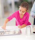 Baking with parent little girl cookies in kitchen Royalty Free Stock Image