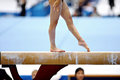 Balance beam legs of a gymnast are seen during an exercise on the apparatus Royalty Free Stock Images