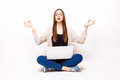 Balance in at work: Young pretty woman sitting in lotus posture on floor with laptop Royalty Free Stock Photo