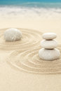 Balance zen stones in sand with sea background Royalty Free Stock Images