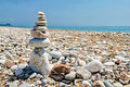 Balancing stones on the beach zen stacked at against a blue sky and ocean with copy space Stock Images