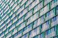 Balconies and windows of a building, apartment houses textured beige green lattices. Royalty Free Stock Photo