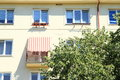 Balcony with sunshade of yellow building behind green tree Stock Image