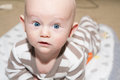 Bald baby with big blue eyes lying on his stomach Royalty Free Stock Photography
