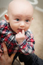 Bald baby boy chewing on finger happy with big blue eyes wide open with a in his mouth looking upward wearing a plaid shirt Royalty Free Stock Photo