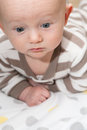 Bald baby looking down with big blue eyes lying on his stomach Stock Image