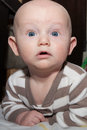 Bald blue eyed baby chubby boy with eyes up close on his stomach Royalty Free Stock Images