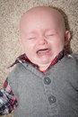 Bald crying baby with mouth open and eyes closed up close his gums and tongue are visible Stock Photography