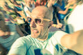 Bald funny man taking a selfie in the crowd with tongue out Royalty Free Stock Photo