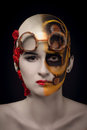 Bald girl with a art make up and steampunk glasses on the one hand mechanical robot on the other blooming desert Royalty Free Stock Image