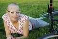 Bald girl with glasses woman lying on the grass bicycle Stock Photography