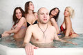 A bald man with four beautiful girls in swimsuits men at the pool Royalty Free Stock Photos