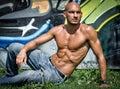 Bald young man shirtless outdoors sitting Royalty Free Stock Photo
