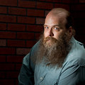 A balding middle aged man with a big bearded against a brick wall looks into the camera with his light blue eyes Royalty Free Stock Photography