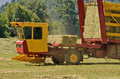 Bale wagon self contaned hay picking up bales of alfalfa from a farm field Stock Photography