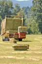 Bale wagon self contaned hay picking up bales of alfalfa from a farm field Royalty Free Stock Photography