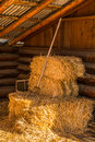 Bales of straw hay with pitchfork in barn warmly sunlit stack golden a sits a log vertical Stock Photos