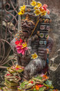 Bali statue of a god covered with flower and incense in ubud indonesia Royalty Free Stock Photography