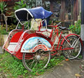 Balinese bicycle tuk tuk or cyclo tied up outside its owners house in sanur bali indonesia Stock Photos