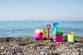 Ball, buckets, rake and shovel toys on a beach near the s Royalty Free Stock Photo