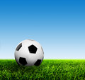 Ball on grass against blue sky. Football, soccer. Royalty Free Stock Photo