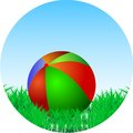 Ball is in the green grass children s lies a on a background of blue sky Stock Photos